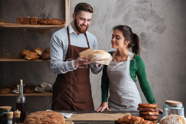 Happy loving couple bakers standing at bakery holding bread Stock photo © deandrobot