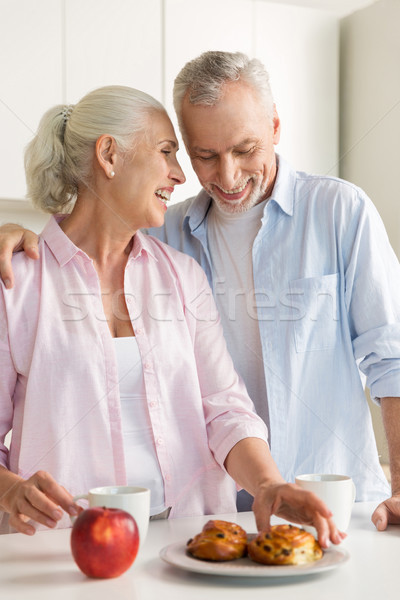 Smiling mature loving couple family standing at the kitchen Stock photo © deandrobot