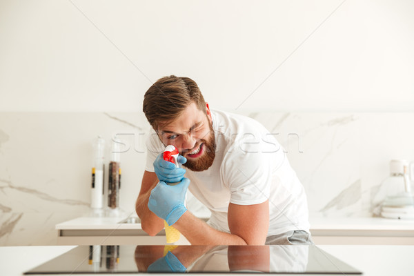 Funny bearded man with cleaners on kitchen Stock photo © deandrobot