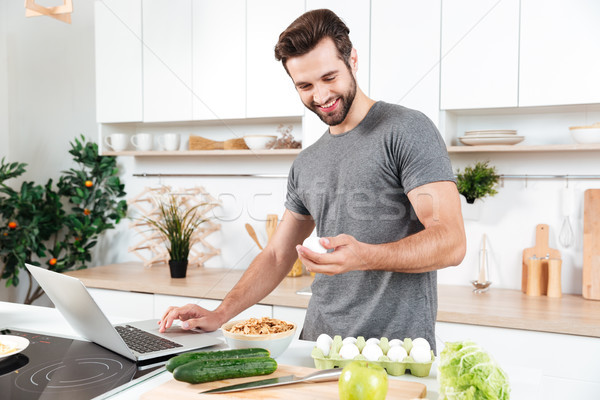Man with laptop preparing food at the kitchen Stock photo © deandrobot