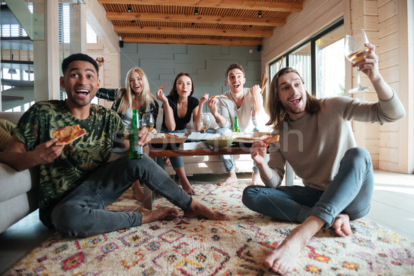 Screaming Happy Five friends sitting in house and eating pizza Stock photo © deandrobot