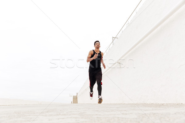 Young african sports man running outdoors. Stock photo © deandrobot