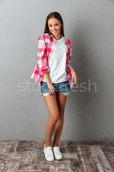 Full length photo of pretty smiling young woman in checkered shi Stock photo © deandrobot