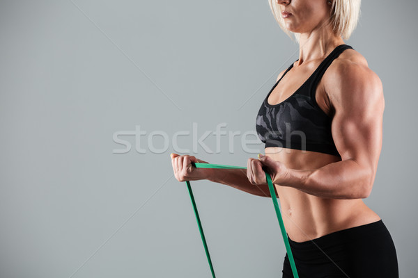 Cropped photo of female bodybuilder stretching with elastic rubb Stock photo © deandrobot