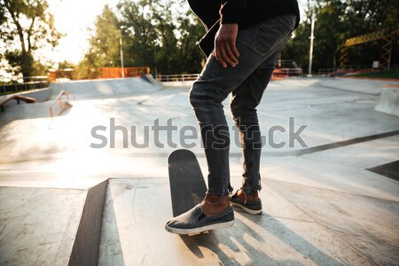 Cropped image of a young male teenager riding a skateboard Stock photo © deandrobot