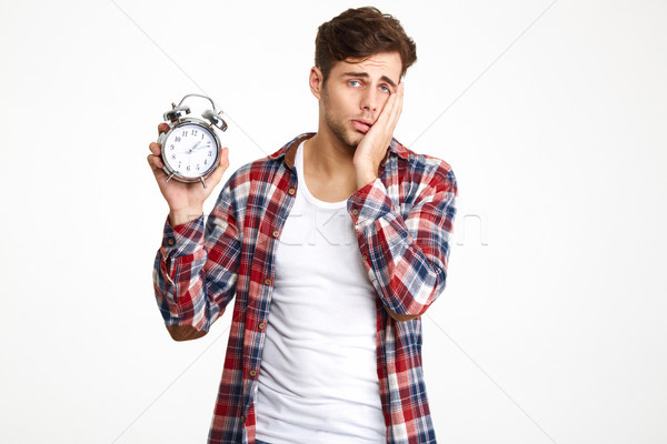 Portrait of a troubled man holding alarm clock Stock photo © deandrobot