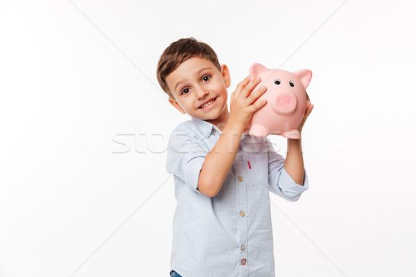 Portrait of a joyful cute little kid holding piggy bank Stock photo © deandrobot