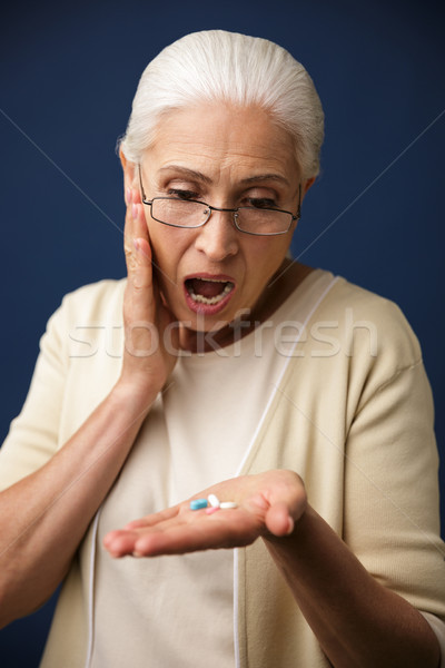 Shocked woman over dark blue background looking at pills. Stock photo © deandrobot