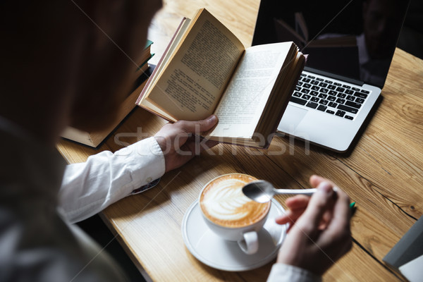 Top view of man in white shirt stirring coffee while reading boo Stock photo © deandrobot