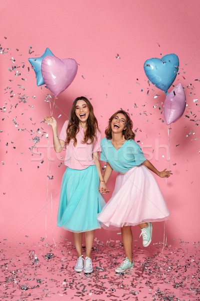 Full length of two overjoyed young woman with balloons in colorf Stock photo © deandrobot