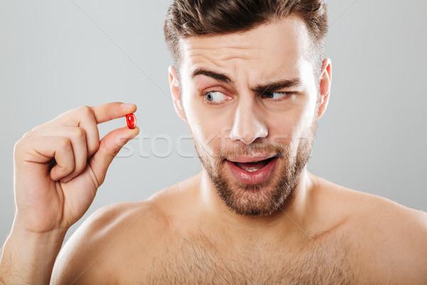 Portré fiatalember néz piros kapszula izolált Stock fotó © deandrobot
