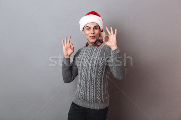 Pleased man in sweater and christmas hat showing ok signs Stock photo © deandrobot