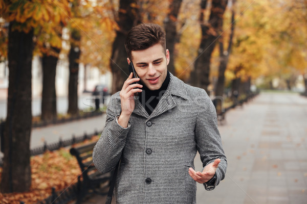 Picture of elegant male in coat walking in empty park with autum Stock photo © deandrobot