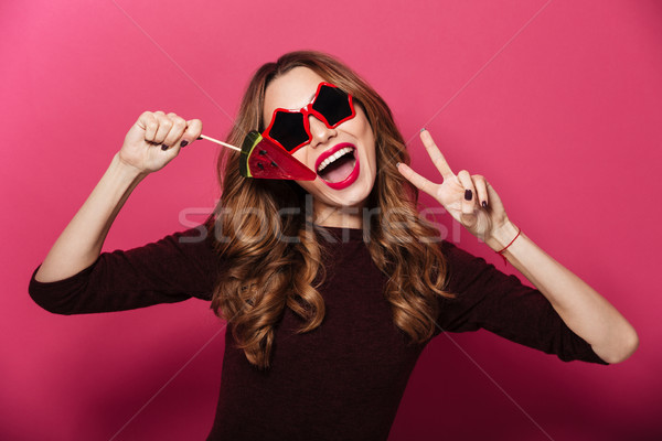 Beautiful lady wearing glasses eating candy make peace gesture. Stock photo © deandrobot