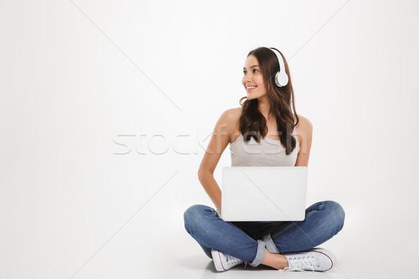 Photo jolie femme écouter de la musique casque portable Photo stock © deandrobot