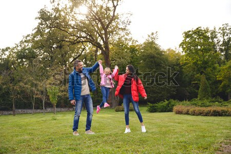 Cheerful young family of three spending time together Stock photo © deandrobot