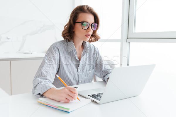 молодые концентрированный брюнетка женщину очки ноутбука Сток-фото © deandrobot