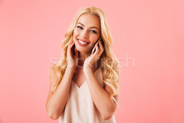 Pleased blonde woman in pajamas talking by smartphone Stock photo © deandrobot