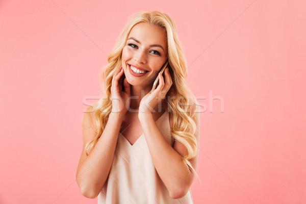 Tevreden blonde vrouw pyjama praten smartphone naar Stockfoto © deandrobot