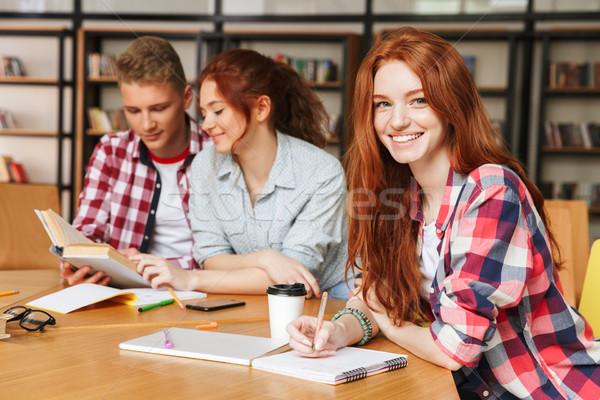 Gruppe Jugendliche Hausaufgaben Sitzung Bibliothek Handy Stock foto © deandrobot
