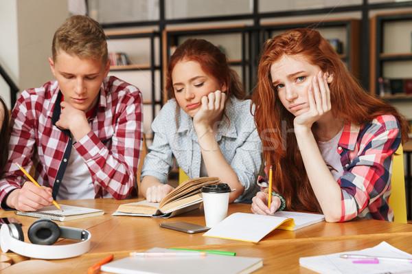 Groep moe tieners huiswerk vergadering bibliotheek Stockfoto © deandrobot
