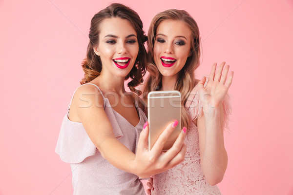 Photo of two young party women smiling and waving hand at camera Stock photo © deandrobot