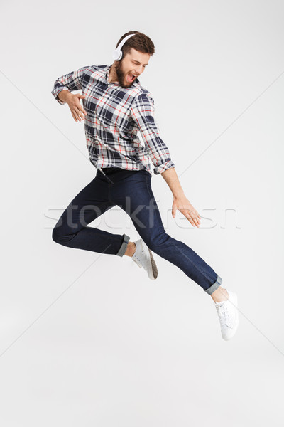 Full length portrait of a happy young man in plaid shirt Stock photo © deandrobot