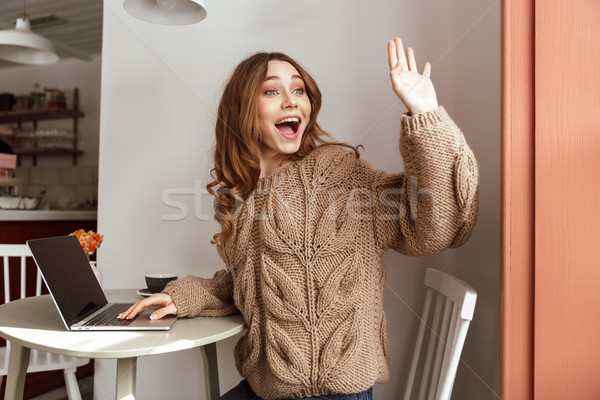 Caucasian woman 20s in casual welcoming with waving hand while s Stock photo © deandrobot
