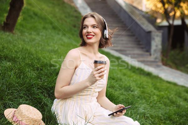 Kobieta sukienka słuchawki pitnej kawy szczęśliwy Zdjęcia stock © deandrobot