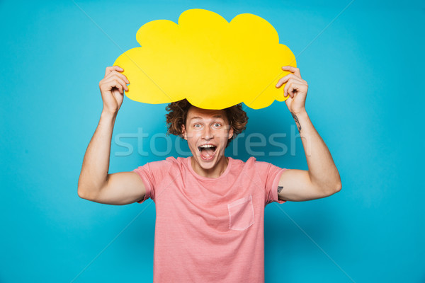 Photo of young excited man 20s with brown curly hair shouting an Stock photo © deandrobot