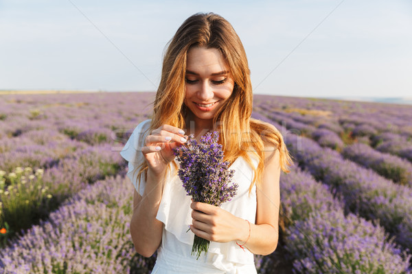 Stock photo: Photo of attractive young woman in dress holding bouquet of flow