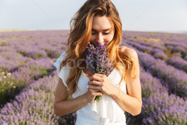 Stock photo: Photo of caucasian young woman in dress holding bouquet of flowe