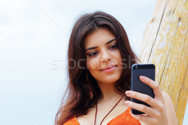 Happy young woman using her smartphone on the beach Stock photo © deandrobot