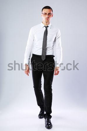 Full-length portrait of confident businessman on gray background Stock photo © deandrobot