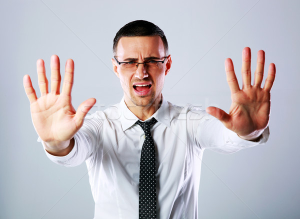 Dissatisfied businessman gesturing stop sign with both hands on gray background Stock photo © deandrobot
