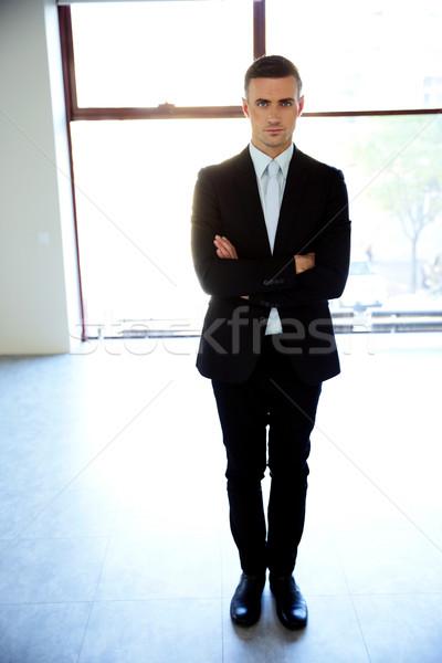 Retrato empresário em pé brasão dobrado Foto stock © deandrobot