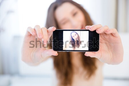 Smiling woman making selfie photo on smartphone at home Stock photo © deandrobot