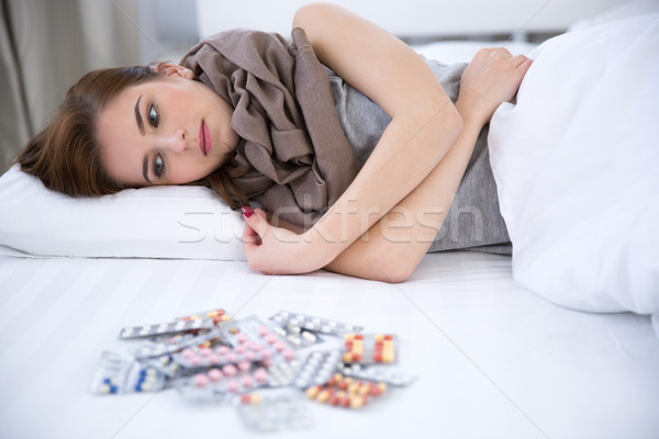 Sick young woman lying on the bed at home Stock photo © deandrobot