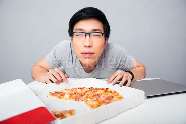 Young asian man smelling pizza Stock photo © deandrobot