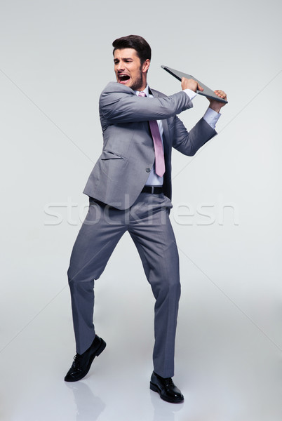Angry businessman trying to smash his laptop Stock photo © deandrobot
