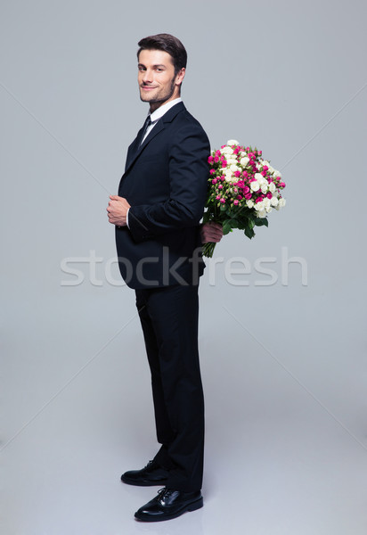 Stock photo: Businessman hiding bouquet of flowers behind his back