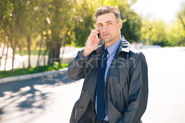 Thoughtful businessman talking on the phone outdoors Stock photo © deandrobot