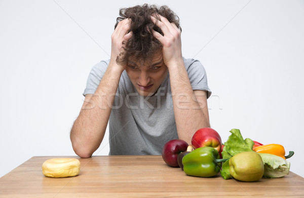 Pensive man sitting at the table with vegetables and donut Stock photo © deandrobot