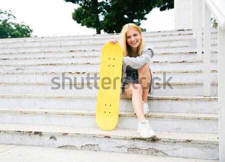 Smiling female skater in sunglasses looking up Stock photo © deandrobot