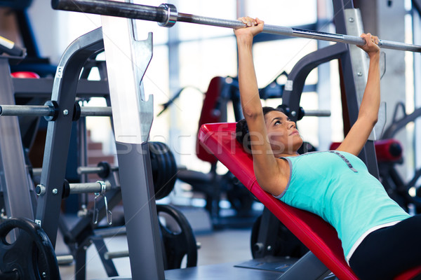 Stock photo: Woman doing exercises with barbell on the bench