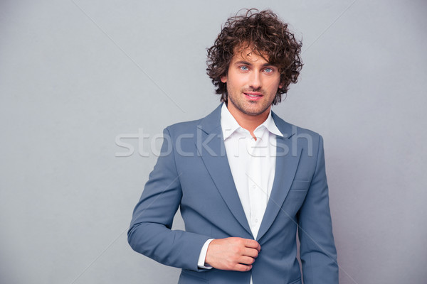 Businessman with curly hair looking at camera  Stock photo © deandrobot