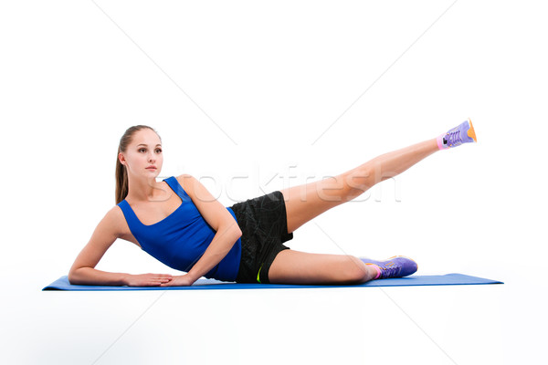 Young sportswoman in sportwear doing exercises for legs Stock photo © deandrobot