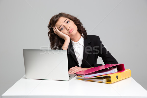 Bored sad young woman using laptop and working with documents Stock photo © deandrobot