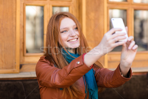 Happy smiling  woman with long red hair making selfie  Stock photo © deandrobot