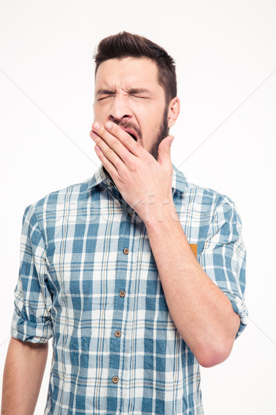 Tired exhausted bearded young man standing and yawning Stock photo © deandrobot
